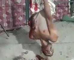 男が拷問として逆さまに吊るされて血を流す